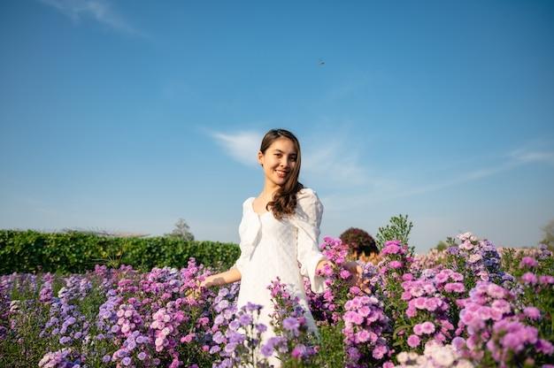 Schöne junge asiatische frau im weißen kleid, die margaretblume genießt, die im garten auf der sonnigen blüht