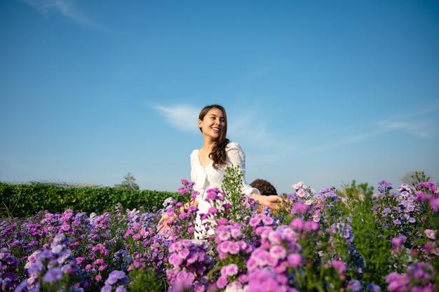 Schöne junge asiatische frau im weißen kleid, die margaretblume genießt, die im garten auf sonnig blüht