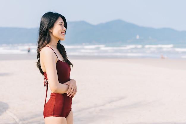 Schöne junge asiatische frau in der badebekleidung, die am strand während der sommerferien entspannt