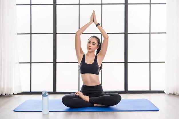 Schöne junge asiatische frau in der yoga-klasse