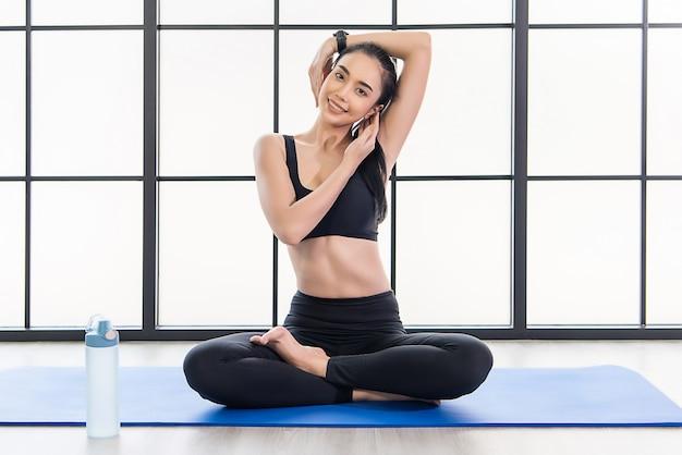 Schöne junge asiatische frau in der yoga-klasse Premium Fotos