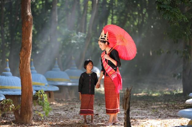 Schöne junge asiatische frau in traditioneller einheimischer kleidung und elefanten im wald des dorfes