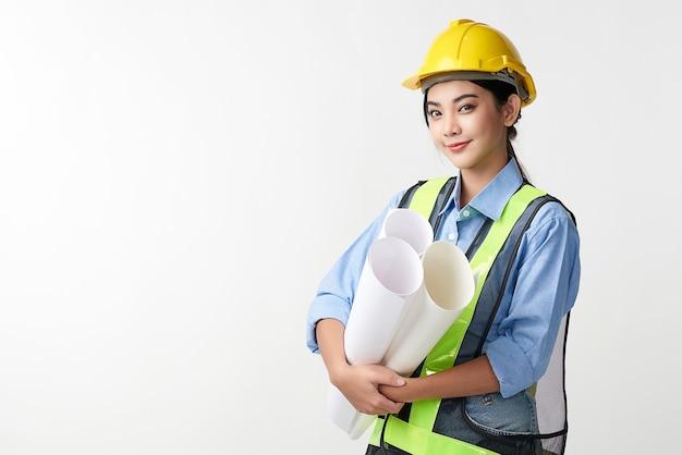 Schöne junge asiatische frau ingenieur und schutzhelm auf weißem hintergrund, baukonzept, ingenieur, industrie.