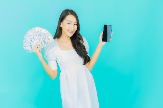 Schöne junge asiatische frau lächelt mit viel bargeld und geld auf blau