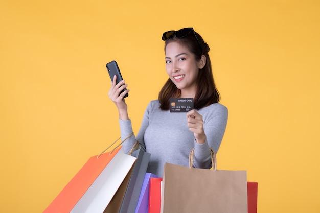 Schöne junge asiatische frau mit bunten einkaufstaschen mit smartphone und kreditkarte lokalisiert auf gelber wand