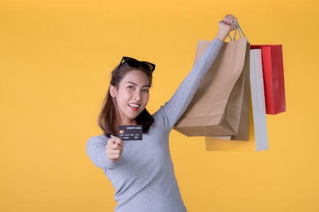 Schöne junge asiatische frau mit bunten einkaufstaschen und kreditkarte lokalisiert auf gelber wand