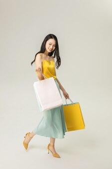 Schöne junge asiatische frau mit einkaufstüten isoliert
