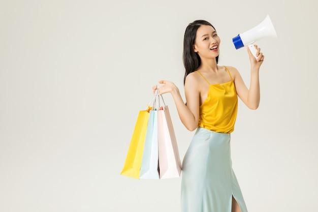 Schöne junge asiatische frau mit einkaufstüten und lautsprechern isoliert