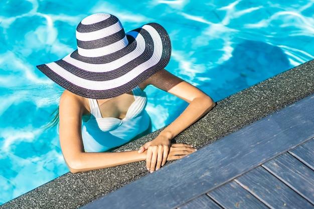 Schöne junge asiatische frau mit hut im swimmingpool für reise und ferien