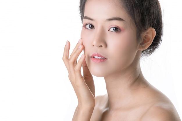 Schöne junge asiatische frau mit kosmetik auf eigenem gesicht