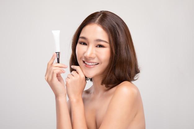 Schöne junge asiatische frau mit kurzen haaren, die luxus weißes sauberes rohrlächeln hält, das so glücklich und fröhlich mit gesunder sauberer und frischer haut fühlt