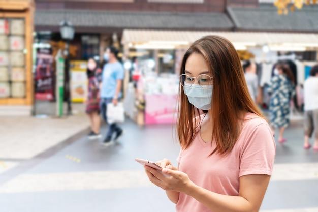 Schöne junge asiatische frau mit ptotective gesichtsmaske unter verwendung des smartphones im einkaufszentrum oder kaufhaus, verwischen hintergrund
