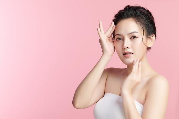 Schöne junge asiatische frau mit sauberer frischer haut auf rosafarbenem hintergrund, gesichtspflege, gesichtsbehandlung, kosmetik, schönheit und spa, asiatisches frauenporträt.