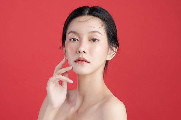 Schöne junge asiatische frau mit sauberer frischer haut auf rotem hintergrund, gesichtspflege, gesichtsbehandlung, kosmetik, schönheit und spa, asiatisches frauenporträt.