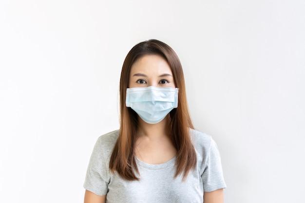 Schöne junge asiatische frau mit schützender gesichtsmaske auf weißer wand