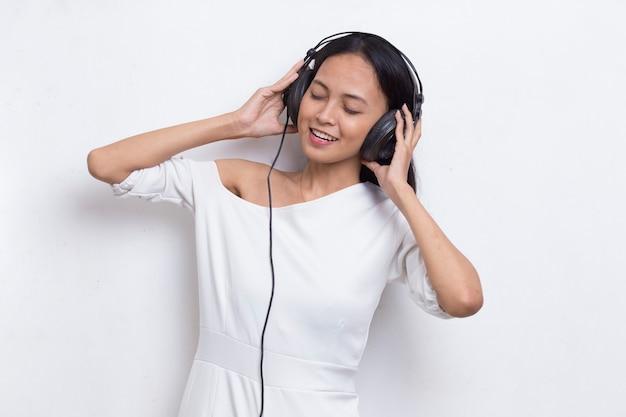 Schöne junge asiatische frau musikhören isoliert auf weißem hintergrund