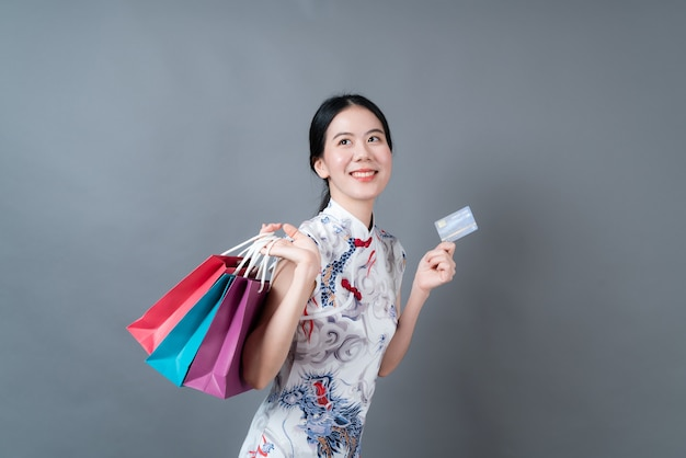 Schöne junge asiatische frau trägt chinesisches traditionelles kleid mit einkaufstasche und kreditkarte auf grauem hintergrund