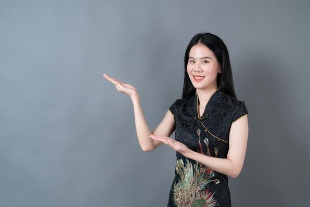 Schöne junge asiatische frau trägt schwarzes chinesisches traditionelles kleid mit der hand, die auf der seite im grauen hintergrund präsentiert