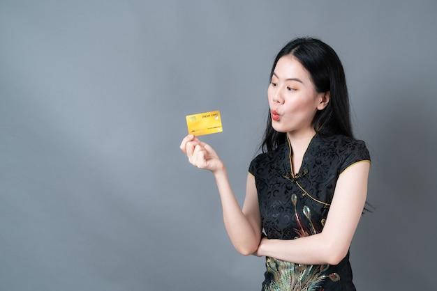 Schöne junge asiatische frau trägt schwarzes chinesisches traditionelles kleid mit der hand, die kreditkarte auf grauem hintergrund hält