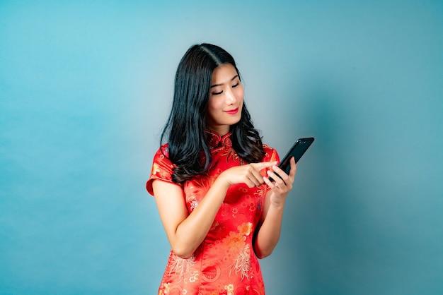 Schöne junge asiatische frau tragen rotes chinesisches kleid mit smartphone