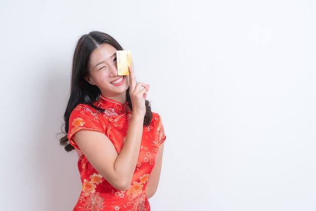 Schöne junge asiatische frau tragen rotes chinesisches traditionelles kleid, das kreditkarte für chinesisches neues jahr mit weißem hintergrund hält