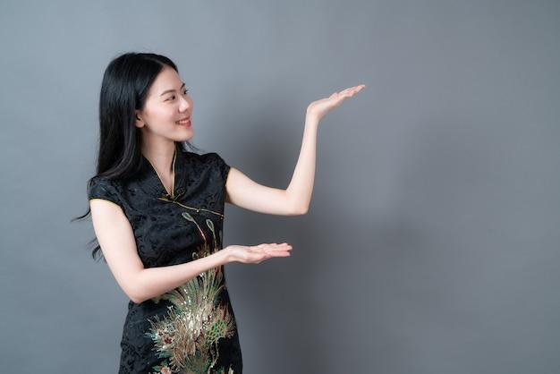Schöne junge asiatische frau tragen schwarzes chinesisches traditionelles kleid mit hand, die auf seite in grauer oberfläche präsentiert