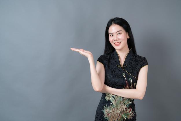 Schöne junge asiatische frau tragen schwarzes chinesisches traditionelles kleid mit handpräsentation