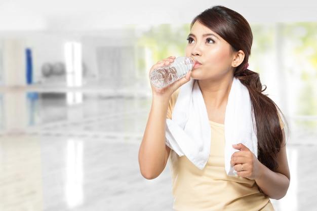 Schöne junge asiatische frau trinken mineralwasser nach dem training