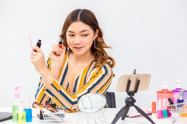 Schöne junge asiatische frau, vlogger, die ihr make-up aufsetzt, während sie schönheitsprodukte auf einem videoblog zu hause überprüft
