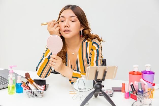 Schöne junge asiatische frau, vlogger, die ihr make-up und lidschatten aufsetzt, während sie schönheitsprodukte auf einem videoblog zu hause überprüft