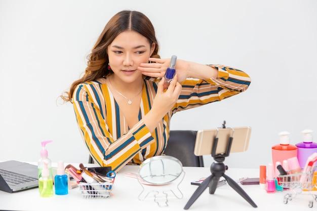 Schöne junge asiatische frau, vlogger, die schönheitsprodukte auf einem videoblog zu hause zeigt und prüft, indem sie ihr telefon verwendet, um live-stream