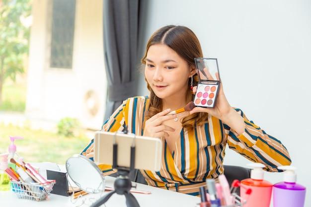 Schöne junge asiatische frau, vlogger, die schönheitsprodukte live auf ihrem videoblog zu hause bewertet