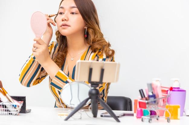 Schöne junge asiatische frau, vlogger, make-up auf, während schönheitsprodukte auf einem videoblog zu hause überprüfen