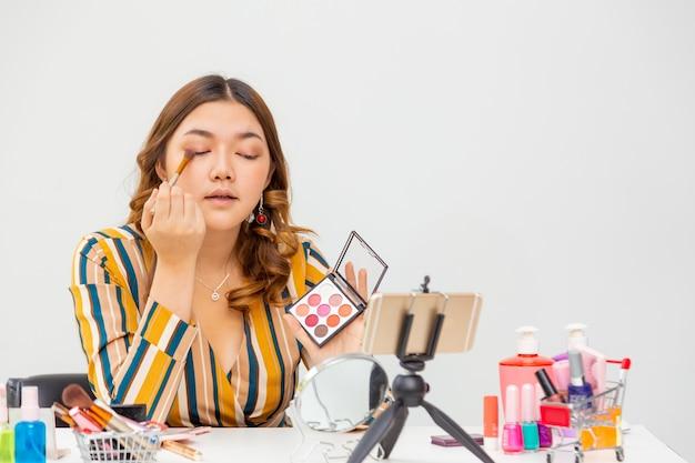 Schöne junge asiatische frau, vlogger, make-up und lidschatten beim überprüfen von schönheitsprodukten auf einem videoblog zu hause, raum für kopierraum