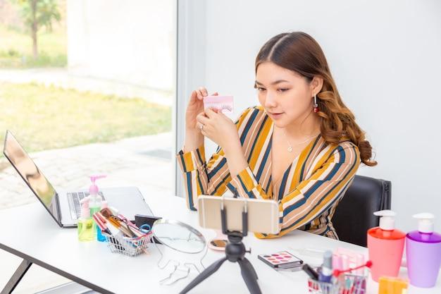 Schöne junge asiatische frau, vlogger, zeigt wimpernverlängerung beim überprüfen von schönheitsprodukten auf einem videoblog