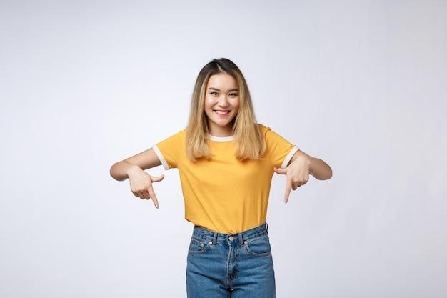 Schöne junge asiatische frau zeigen nach unten