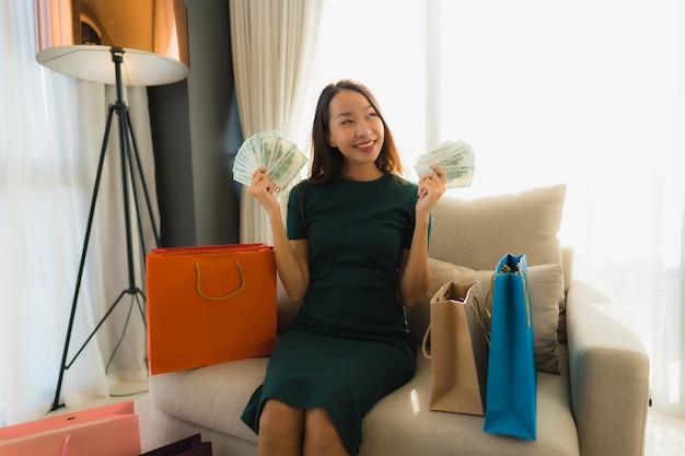 Schöne junge asiatische frauen des porträts, die kreditkarte für das on-line-einkaufen verwenden