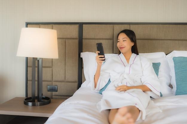Schöne junge asiatische frauen des porträts, die mobile auf bett verwenden