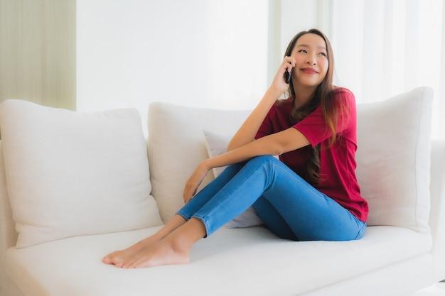 Schöne junge asiatische frauen des porträts, die mobile oder intelligentes telefon auf sofa verwenden