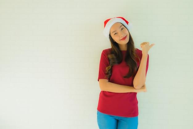Schöne junge asiatische frauen des porträts, die sankt-hut für feier im weihnachten tragen