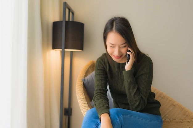 Schöne junge asiatische frauen des porträts, die unterhaltungshandy verwenden und auf sofastuhl sitzen
