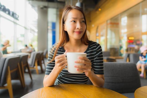 Schöne junge asiatische frauen des porträts im kaffeestubecafé und -restaurant mit handy