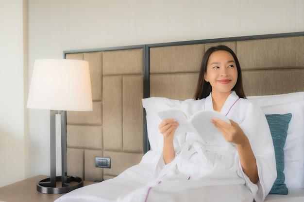 Schöne junge asiatische frauen des porträts mit buch auf bett