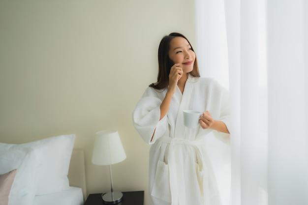 Schöne junge asiatische frauen des porträts mit kaffeetasse und handy