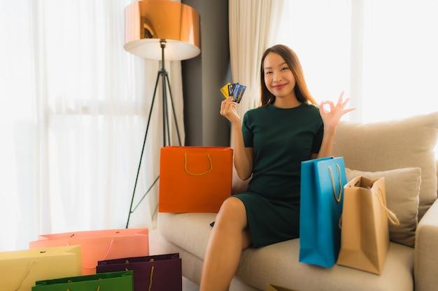 Schöne junge asiatische frauen des porträts mit kreditkarte für das on-line-einkaufen
