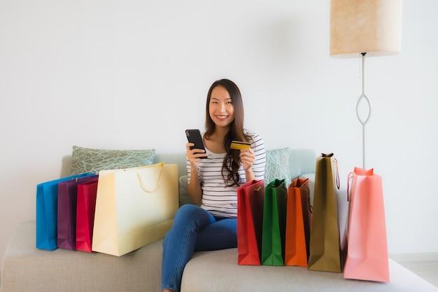 Schöne junge asiatische frauen des porträts mit kreditkarte handy oder computer für den einkauf