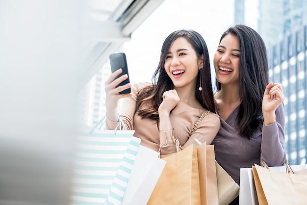 Schöne junge asiatische frauen, die selfie nehmen, nachdem sie den einkauf in der stadt genossen haben