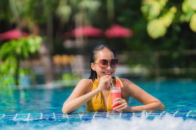 Schöne junge asiatische frauenfreizeit des porträts entspannen sich lächeln mit wassermelonensaft um swimmingpool im hotelerholungsort