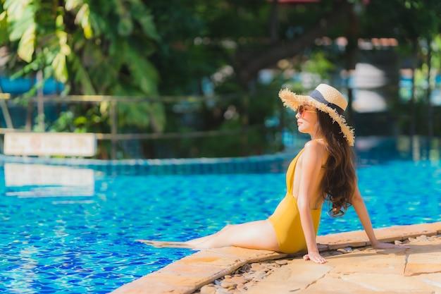 Schöne junge asiatische frauenfreizeit des porträts entspannen sich lächeln und glücklich um swimmingpool im hotelerholungsort