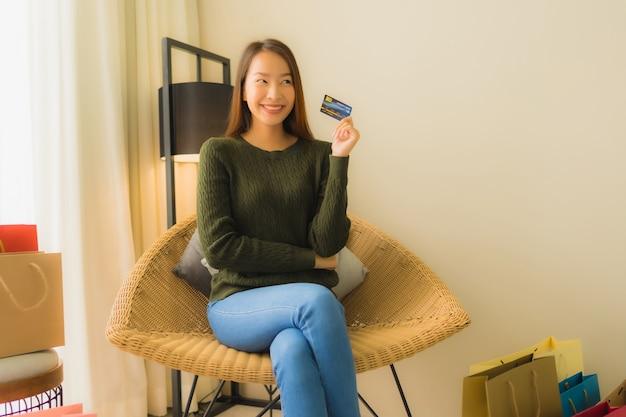 Schöne junge asiatische frauenkreditkarte des porträts für das on-line-einkaufen